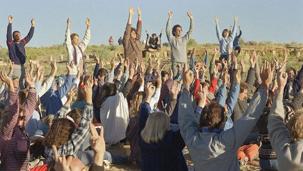 "Celebrants raise their hands as the sun rises over the northwestern New Mexico landscape near Chaco Canyon, N.M., Aug. 16, 1987. About a thousand people participated in various activities, part of the ""harmonic convergence"" including chanting, prayer and meditation. (AP Photo/David Breslauer)"